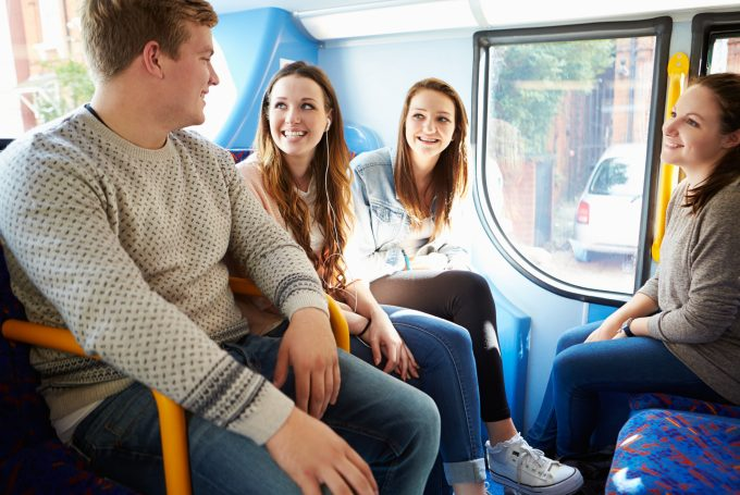 Group Of  Happy Smiling Young People On Bus Journey Together
